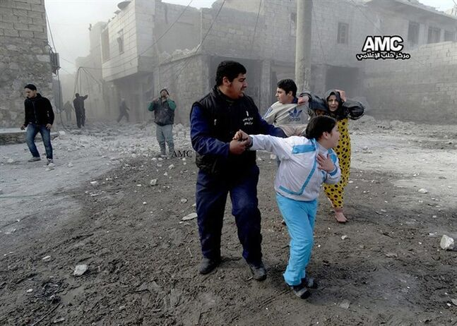In this picture taken on Friday Jan. 31, 2014, a citizen journalism image provided by Aleppo Media Center (AMC), an anti-Bashar Assad activist group, and authenticated based on its contents and other AP reporting, Syrian family members run in the street following an attack by a Syrian government forces warplane, in Aleppo, Syria. Syrian military helicopters dropped barrels packed with explosives on rebel-held areas of the northern city of Aleppo on Saturday, killing at least a dozen of people including a family trapped in a car, as government forces inched closer to opposition-held areas. (AP Photo/Aleppo Media Center, AMC)