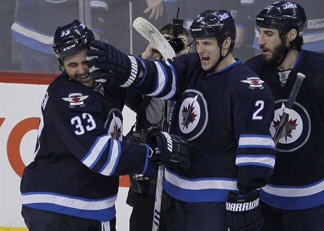 Winnipeg Jets' Dustin Byfuglien (33) and Adam Pardy (2) celebrate Byfuglien's overtime goal to beat the Toronto Maple Leafs 5-4 in NHL action in Winnipeg on Saturday, January 25, 2014. THE CANADIAN PRESS/John Woods