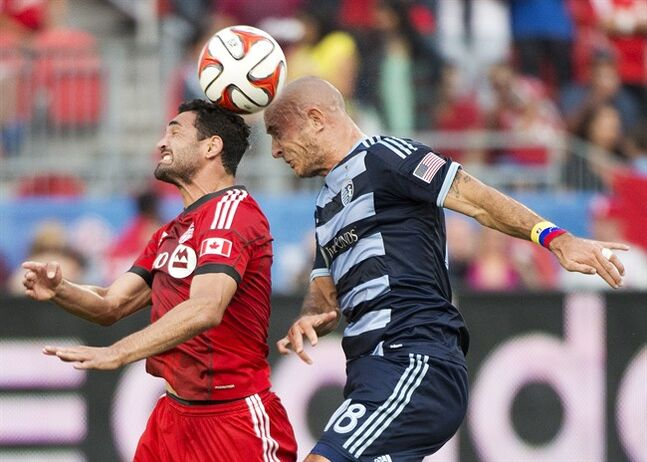 Toronto FC forward Gilberto, left, heads the ball with Sporting Kansas City midfielder Victor Munoz, right, during first half MLS soccer action in Toronto on Saturday, July 26, 2014. THE CANADIAN PRESS/Nathan Denette