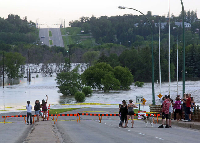Passersby look at the portion of First Street North covered by floodwaters of the Assiniboine River on Sunday night. The closure — likely to remain in effect until at least July 17, when the river is expected to crest again — is taking a toll on motorists and area businesses.