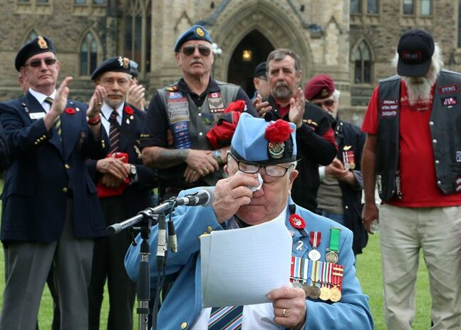 Emotional war veteran Ron Clarke wipes away tears as he addresses fellow veterans during a war veterans rally on Parliament Hill in Ottawa, Wednesday June 4, 2014. THE CANADIAN PRESS/Fred Chartrand