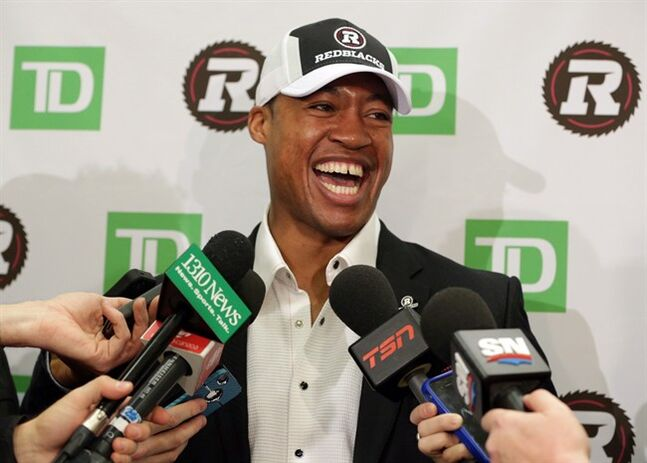 Henry Burris has a laugh with members of the media at a news conference in Ottawa, Tuesday, Feb.4, 2014, where the CFL's Redblacks announced they had signed the veteran quarterback as a free agent. THE CANADIAN PRESS/Mike Carroccetto