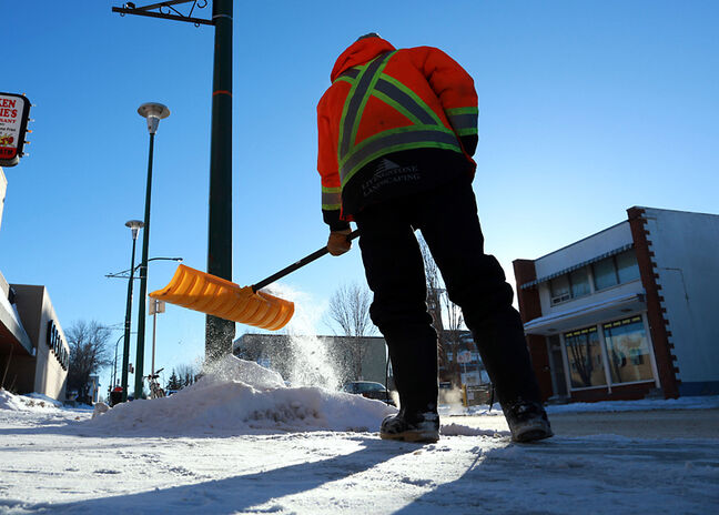 Chanelle Davis clears the sidewalk along Rosser Avenue under the last rays of the afternoon sun on Monday. Davis and other co-workers from Livingstone Landscaping were clearing the way near the downtown bus depot.