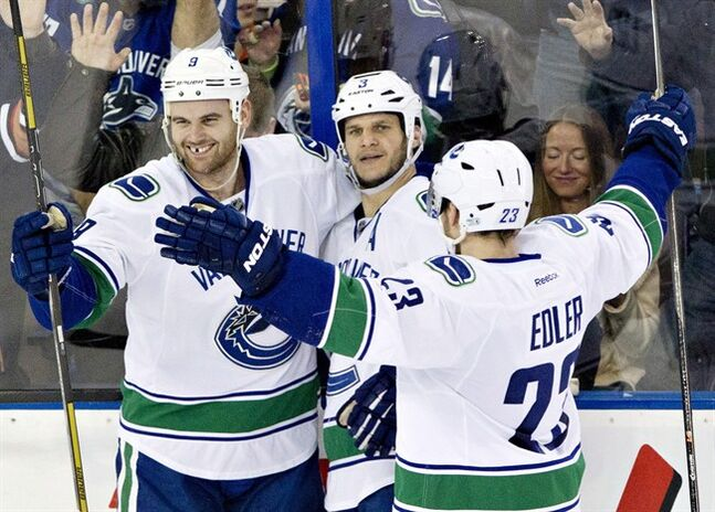 Vancouver Canucks' Zack Kassian (9), Kevin Bieksa (3), Alexander Edler (23) celebrate a goal against the Edmonton Oilers during second period NHL hockey action in Edmonton, Alta., on Tuesday January 21, 2014. THE CANADIAN PRESS/Jason Franson