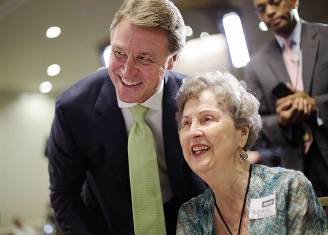 Georgia Republican Senate candidate, David Perdue, left, talks with his mother Gervaise Perdue, at an election night party while waiting for results from Georgia's primary election, Tuesday, May 20, 2014, in Atlanta. Five major GOP candidates will square off to represent their party this fall in the election to replace retiring U.S. Sen. Saxby Chambliss. Meanwhile, Michelle Nunn - daughter of former U.S. Sen. Sam Nunn, is a heavy favorite to win the Democratic nomination. (AP Photo/David Goldman)