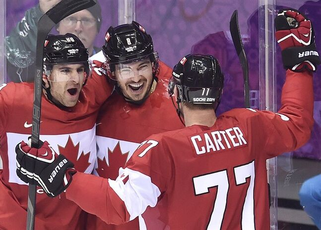 Canada defenceman Drew Doughty, centre, celebrates with teammates John Tavares (20) and Jeff Carter (77) after scoring the game-winning goal in overtime against Finland during preliminary round hockey action at the 2014 Sochi Winter Olympics in Sochi, Russia on Sunday, February 16, 2014. THE CANADIAN PRESS/Nathan Denette