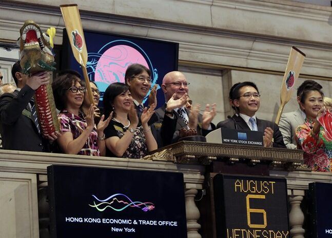 Stephen Barclay, center, director of the Hong Kong Economic and Trade Office, is joined in applause during New York Stock Exchange opening bell ceremonies, Wednesday, Aug. 6, 2014, to mark the upcoming 24th Annual Hong Kong Dragon Boat Festival. (AP Photo/Richard Drew)