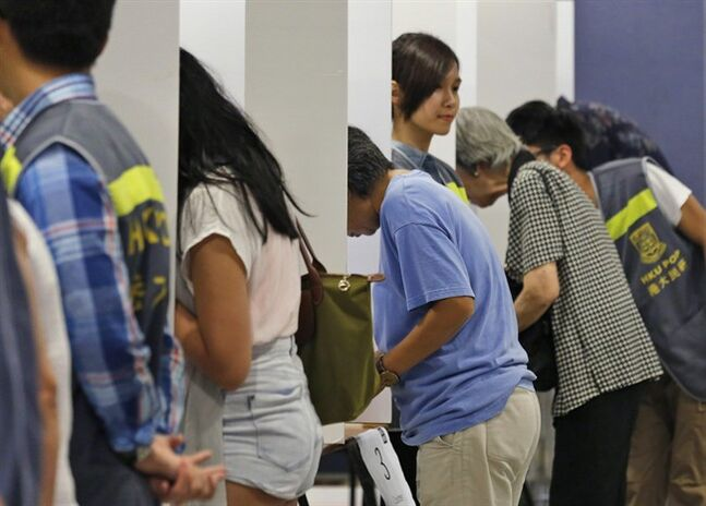 People vote in a polling station for an unofficial referendum on democratic reform in Hong Kong Sunday, June 22, 2014. More than half a million Hong Kongers have voted in an unofficial referendum on democratic reform in the specially administered Chinese city that Beijing has blasted as illegal. (AP Photo/Kin Cheung)
