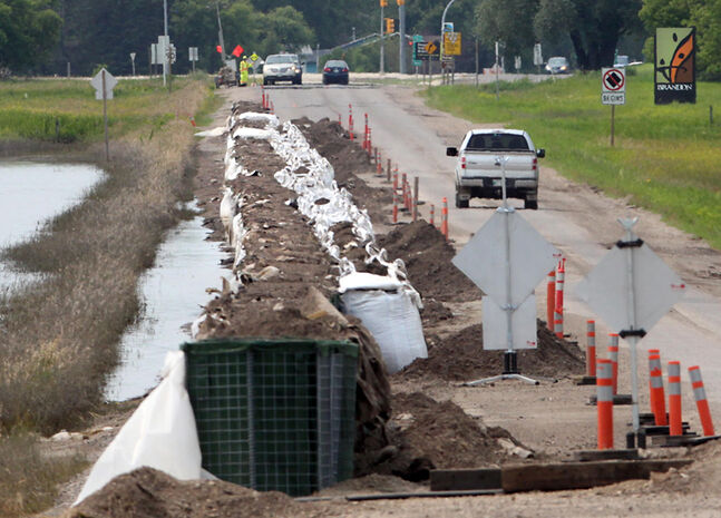 Sandbags and an earthen barrier line the eastbound lane of Veterans Way on Thursday afternoon. The high waters of the flooded Assiniboine River also caused sandbags to sprout up at the nearby Brandon Correctional Centre.
