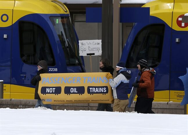 Climate change activists rallied outside the Union Depot in St. Paul, Minn., Wednesday, Feb. 26, 2014 prior to the visit of President Barack Obama. They urged Obama to reject the proposed Keystone XL oil pipeline from Canada to the Gulf Coast and say oil trains from North Dakota are disrupting Amtrak traffic. (AP Photo/Jim Mone)