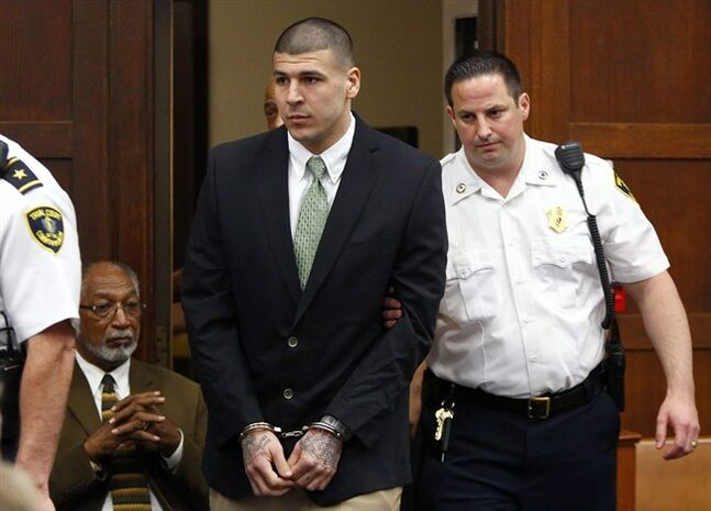 FILE - In this May 28, 2104, file photo, former New England Patriots footballplayer Aaron Hernandez is led into the courtroom to be arraigned on homicide charges at Suffolk Superior Court in Boston. Hernandez's lawyers want a judge to transfer the him to a jail closer to Boston, citing safety and other concerns. In a request filed Friday, June 20, 2014, his Boston-based attorneys say they have to travel too far to meet him at the Bristol County jail. (AP Photo/Dominick Reuter, Pool, File(