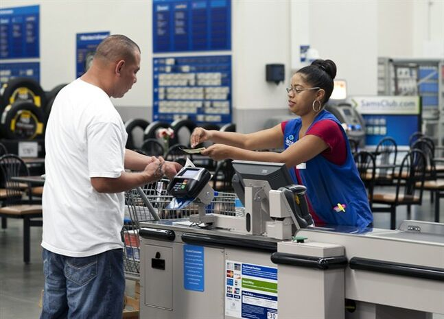 In this June 5, 2014 photo, Conquisia Tyler, right, gives change to a customer at Sam's Club in Bentonville, Ark. The Commerce Department releases personal income and spending for May on Thursday, June 26, 2014. (AP Photo/Sarah Bentham)