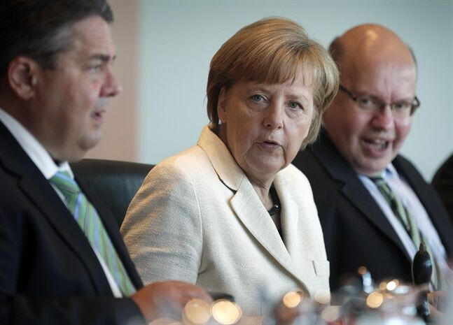 German Chancellor Angela Merkel, center, speaks as she sits between German Economy and Energy Minister Sigmar Gabriel, left, and Peter Altmaier, Head of the Federal Chancellery, right, at the beginning of the weekly cabinet meeting at the chancellery in Berlin, Germany, Wednesday, May 21, 2014. (AP Photo/Michael Sohn)
