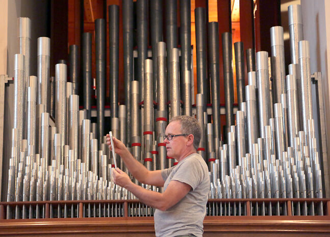 Casavant technician Steve Miller of Calgary works to install a new pipe organ in St. Matthew's Cathedral Church on Tuesday afternoon. The organ comprises more than 2,200 individual lead alloy pipes.