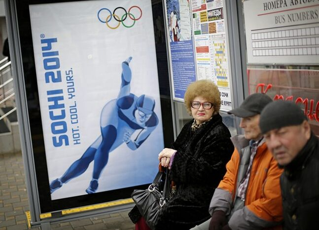 A woman waits for a bus next to a billboard advertising the upcoming 2014 Winter Olympics, Wednesday, Jan. 29, 2014, in Sochi, Russia. (AP Photo/David Goldman)