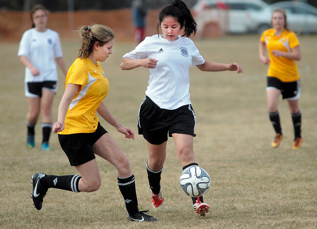 Massey's Kelly Cram (middle) looks to play the ball up the field while being pressured by Crocus's Jenna Wiebe.