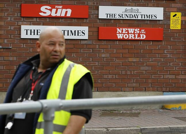 FILE - This is a Thursday, July 14, 2011 file photo of a security guard keeps watch at News International in Wapping, London. Former News of the World editor Andy Coulson was convicted of phone hacking Tuesday, but fellow editor Rebekah Brooks was acquitted after a months long trial centering on illegal activity at the heart of Rupert Murdoch's newspaper empire. The News of the World closed, because of the phone hacking scandal. (AP Photo/Kirsty Wigglesworth, File)