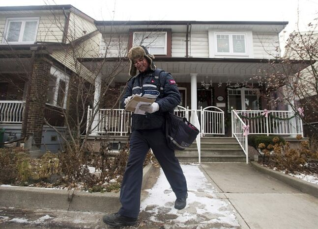 A Canada Post employee delivers mail and parcels to residential homes in Toronto on Wednesday, Dec. 11, 2013. The federal Crown corporation plans to phase out home delivery within the next five years, replacing foot delivery with community mail boxes. Canada Post says says about 6,000 to 8,000 positions will be eliminated over the same time period, mainly through attrition. THE CANADIAN PRESS/Nathan Denette