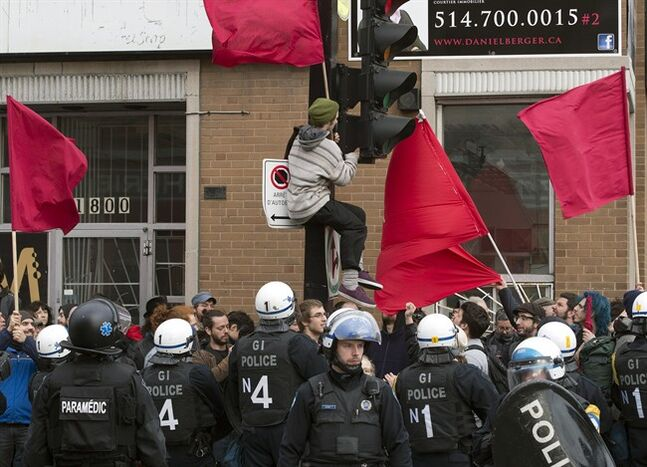 A protester hangs a flag on a lampost as police surround a group of protesters during the annual May Day anti-capitalism demonstration Thursday, May 1, 2014 in Montreal. THE CANADIAN PRESS/Ryan Remiorz