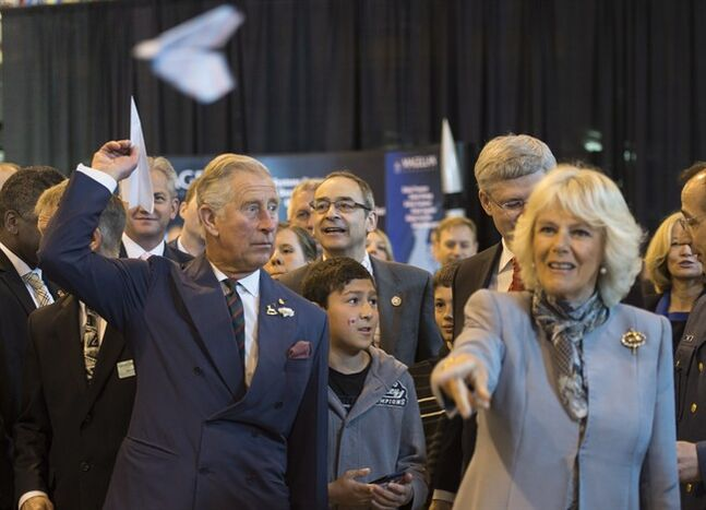 Prince Charles, left, and his wife Camilla throw paper airplanes with Prime Minister Stephen Harper (obscured) during an event to mark aerospace and aviation in Manitoba day in Winnipeg on Wednesday, May 21, 2014. The Royal couple are on a four-day tour of Canada. THE CANADIAN PRESS/Paul Chiasson