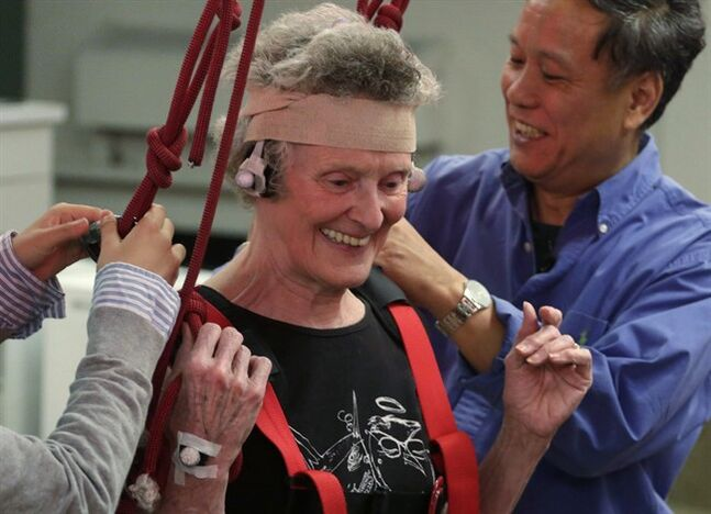 This July 28, 2014 photo shows Mary Kaye, 81, smiling after successfully demonstrating a treadmill balance session at University of Illinois-Chicago. Clive Pai, a physical therapy professor, right, and graduate student Emma Wang, left, un-hook Kaye's safety harness at the end of the session. During the test Kaye walked on a lab-built walkway that causes people to unexpectedly trip and can teach them quickly how to catch themselves and avoid falling. Falls in the elderly cost $30 billion yearly to treat and can send them spiraling into poor health and disability. Pai who came up with the idea calls it