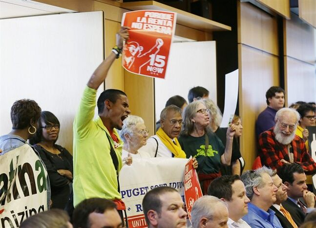 Carlos Hernandez-Sosa, center left, holds a sign in support of Seattle's $15 minimum wage measure, Monday, June 2, 2014, during a meeting of the Seattle City Council, which eventually passed the $15 minimum wage measure later in the meeting. (AP Photo/Ted S. Warren)