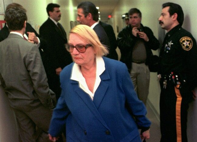 FILE - In this Thursday Feb. 13, 1997, file photo, Vera Coking walks past Donald Trump, partially obscured against wall at left, in a courtroom hallway at Atlantic County Superior Court in Atlantic City, N.J. Coking, who became a folk hero for resisting decades-long efforts by big-name developers like Trump to displace her Atlantic City boardinghouse, is now 91 and, at last, ready to sell. Coking's boardinghouse goes up for auction Thursday, July 31, 2014, for a $199,000 starting bid. (AP Photo/Allen Oliver, File)