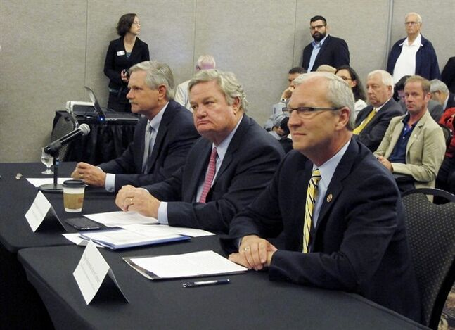 North Dakota Gov. Gov. Jack Dalrymple, center, U.S. Sen. John Hoeven, R-N.D., left, and U.S. Rep. Kevin Cramer. R-N.D., listen to opening statements by the National Surface Transportation Board during a hearing on Thursday, Sept. 4, 2014, in Fargo, N.D. The hearing discussed delays in railroad grain shipments. (AP Photo/Dave Kolpack)