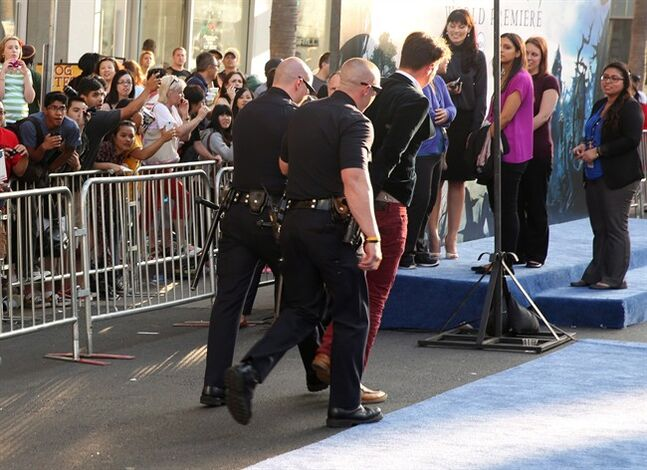Journalist Vitalii Sediuk is walked off carpet in handcuffs after allegedly attacking Brad Pitt at the world premiere of
