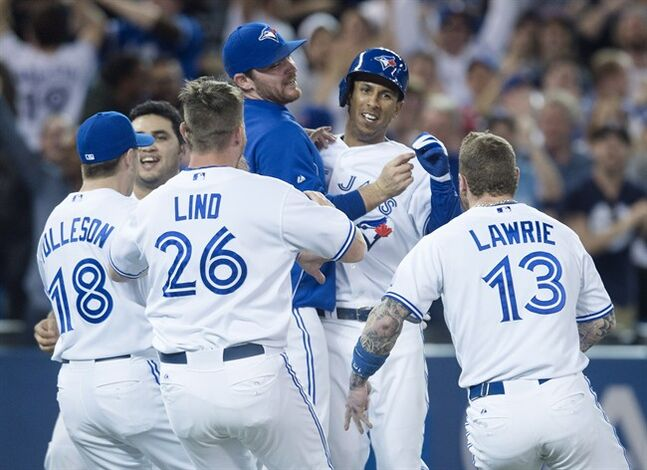 Toronto Blue Jays' Anthony Gose, second from right, is mobbed by teammates after the Blue Jays' walk-off win over the Tampa Bay Rays in the ninth inning of MLB baseball action in Toronto on Wednesday, May 28, 2014. The Blue Jays defeated the Rays 3-2 and have extended their winning streak to nine games. THE CANADIAN PRESS/Darren Calabrese