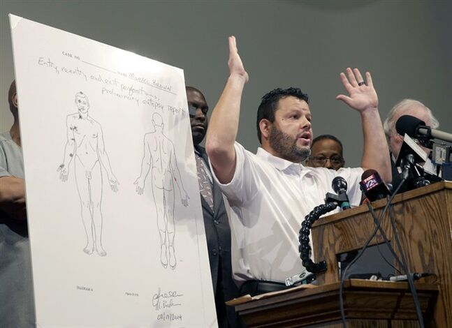 Forensic pathologist Shawn Parcells speaks during a news conference to share preliminary results of a second autopsy done on Michael Brown Monday, Aug. 18, 2014, in St. Louis County, Mo. The independent autopsy shows 18-year-old Michael Brown was shot at least six times, and Parcells, who assisted former New York City chief medical examiner Dr. Michael Baden during the autopsy, said a graze wound on Brown's right arm could have occurred in several ways. (AP Photo/Jeff Roberson)