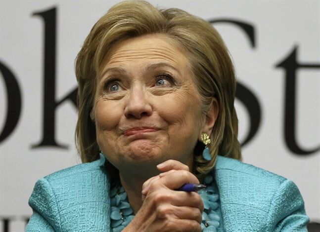FILE - This June 16, 2014 file photo shows former Secretary of State Hillary Rodham Clinton reacting to a customer at a signing for her new book