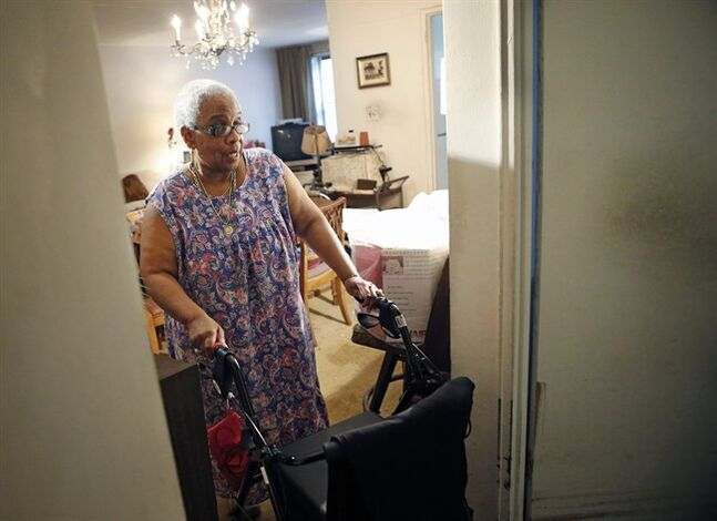 In this July 17, 2014 photo, Carolyn Allen, a 69 year-old widow who has suffered two strokes, makes her way through Marcia Rosenfeld's Ditmas, Brooklyn, apartment in New York. Allen shares Rosenfeld's two-bedroom apartment thanks to a home-sharing program run by a New York-based non-profit agency. (AP Photo/Kathy Willens)