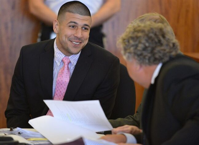 Aaron Hernandez speaks with his lawyer Michael Fee, right, during a hearing in Fall River superior court Monday July 7, 2014, in Fall River, Mass. The Judge agreed that Hernandez could be moved to a jail closer to Boston while he awaits his trial for the murder of Odin Lloyd. (AP Photo/The Boston Globe, Josh Reynolds, Pool)