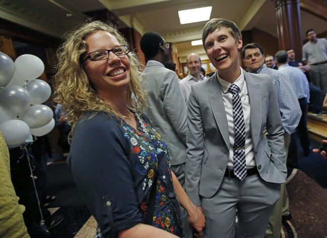 Samantha Paul, left, and Tiffany Elliot of Maynard, Mass. laugh as they attend a celebration held at Cambridge City Hall in Cambridge, Mass., Friday, May 16, 2014, to mark the 10th anniversary of the first same-sex weddings in Massachusetts and the nation. Cambridge was the first city in the country to issue marriage licenses on May 17, 2004. (AP Photo/Elise Amendola)