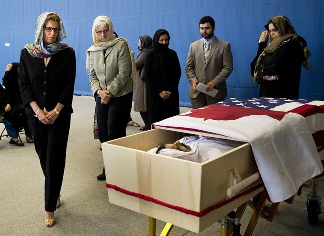 Ontario Premier Kathleen Wynne, left, and her partner Jane Rounthwaite, second left, pay their respects to Dr. Mehdi Ali Qamar, the Canadian-American cardiologist who was assassinated in Pakistan while on a humanitarian mission at his funeral service in Vaughan, Ont., on Wednesday, June 4, 2014. THE CANADIAN PRESS/Nathan Denette