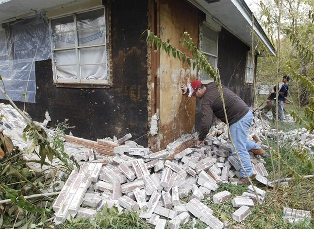 FILE - In this Nov, 6, 2011 file photo, Chad Devereaux examines bricks that fell from three sides of his in-laws home in Sparks, Okla., following two earthquakes that hit the area in less than 24 hours. A study published Thursday, July 3, 2014 by the journal Science explains how just four wells forcing massive amounts of drilling wastewater into the ground are probably causing quakes in Oklahoma. The wells seem to have triggered more than 100 small-to-medium earthquakes in the past five years, according to a study. (AP Photo/Sue Ogrocki, File)