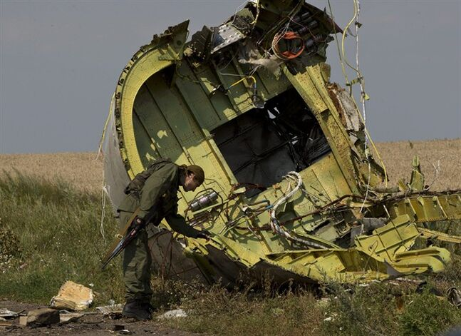 FILE - In this July 22, 2014 file photo, a pro-Russian rebel touches the MH17 wreckage at the crash site of Malaysia Airlines Flight 17, near the village of Hrabove, eastern Ukraine. Japan's top government spokesman said Monday, July 28 that the country is stepping up sanctions against Russia over the unrest in Ukraine. The sanctions include the freezing of assets held in Japan by individuals and groups supporting the separation of Crimea from Ukraine, as well as a ban on Crimean imports, Chief Cabinet Secretary Yoshihide Suga said. The move follows the July 17 downing of Malaysia Airlines Flight 17 in eastern Ukraine. (AP Photo/Vadim Ghirda, File)