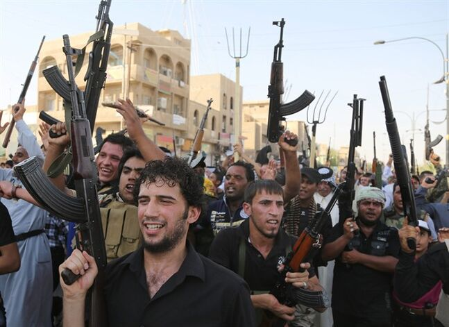 Shiite tribal fighters raise their weapons and chant slogans against the al-Qaida-inspired Islamic State of Iraq and the Levant (ISIL) in the northwest Baghdad's Shula neighborhood, Iraq, Monday, June 16, 2014. Sunni militants captured a key northern Iraqi town along the highway to Syria early on Monday, compounding the woes of Iraq's Shiite-led government a week after it lost a vast swath of territory to the insurgents in the country's north. (AP Photo/ Karim Kadim)