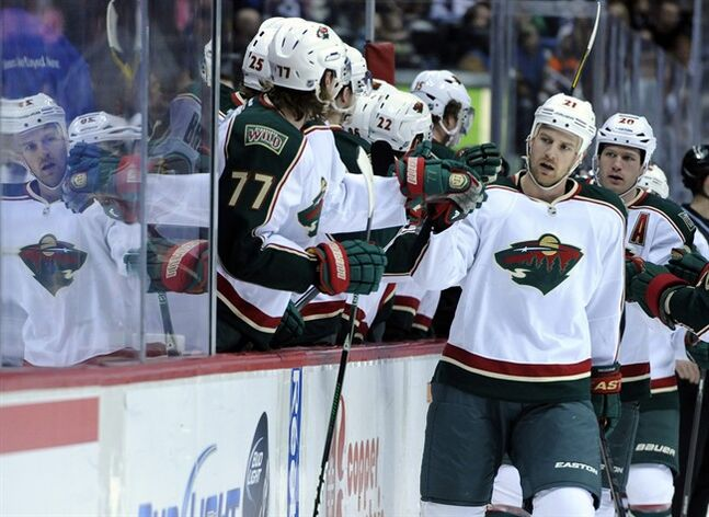 Minnesota Wild center Kyle Brodziak (21) celebrates a goal with teammates on the bench during the first period of an NHL hockey game against the Colorado Avalanche on Saturday, March 16, 2013, in Denver. (AP Photo/Jack Dempsey)