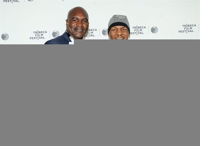 Retired professional boxers Evander Holyfield, left, and Mike Tyson pose together at the