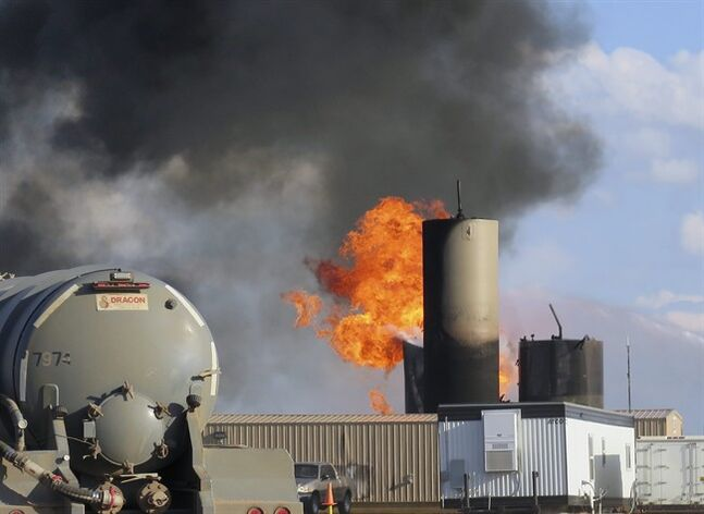 In this Monday, July 7, 2014 file photo, a saltwater disposal facility burns after it was struck by lightning, near Alexander, N.D. Three massive fires since the beginning of June have highlighted the threat lightning poses in the North Dakota oil patch, and in each case it was tanks that store the toxic saltwater associated with drilling, not the oil wells or drilling rigs, that were to blame. (AP Photo/Josh Wood, File)