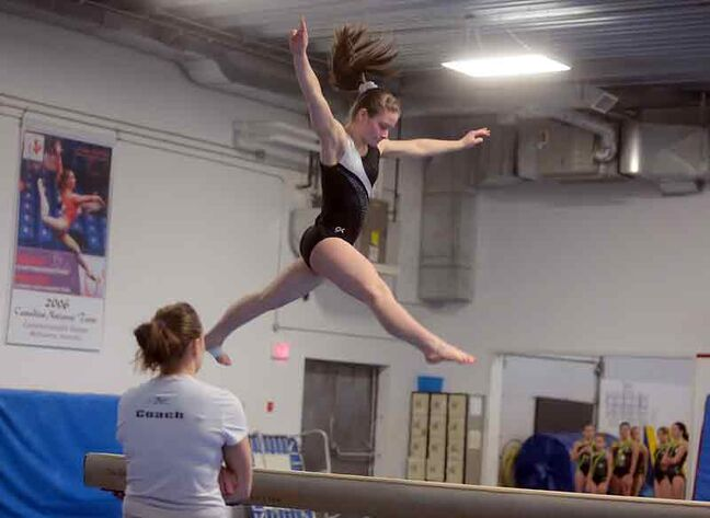 Brandon Eagles gymnast Emma Scott leaps through the air while competing on the beam during the Westman qualifying event for the Manitoba Winter Games at the Brandon Eagles Gymnastics Centre on Sunday.