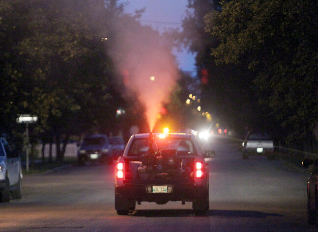 City crews spray malathion along Louise Avenue near 12th Street, during the first round of fogging.