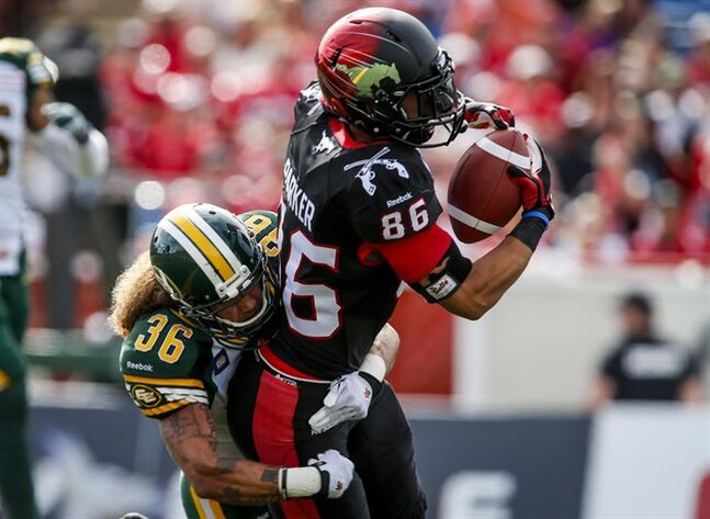 Edmonton Eskimos' Aaron Grymes, left, tries to stop Calgary Stampeders' Anthony Parker, from scoring a touchdown during first half CFL football action in Calgary, Alta., Monday, Sept. 1, 2014. THE CANADIAN PRESS/Jeff McIntosh