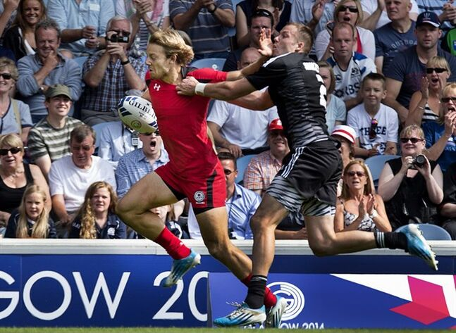 Canada's Harry Jones is tackled by New Zealand's Tim Mikkelson in Commonwealth Games rugby sevens action at Ibrox Stadium in Glasgow, Scotland on Saturday, July 26, 2014. New Zealand won 39-0. THE CANADIAN PRESS/Andrew Vaughan