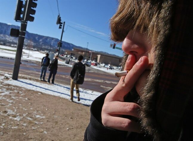 A high school student, who preferred not to be identified, smokes a cigarette in a de facto smoking area just off the property of Lewis-Palmer High School, in Monument, Colo., Thursday Feb. 20, 2014. A proposal to raise the tobacco age to 21 in Colorado is up for its first review in the state Legislature. The bipartisan bill would make Colorado the first with a statewide 21-to-smoke law. (AP Photo/Brennan Linsley)