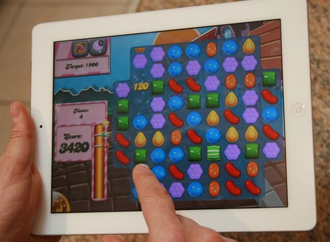 A man plays the computer game Candy Crush Saga on his iPad.