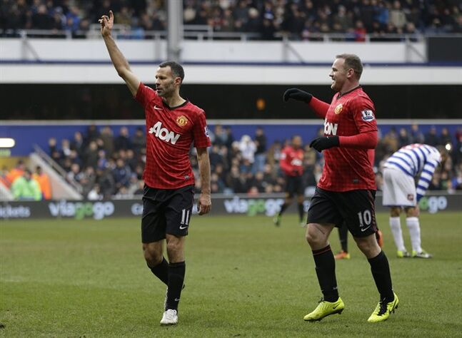 Manchester United's Ryan Giggs, left, celebrates with his teammate Wayne Rooney, right, after he scored against Queens Park Rangers, during their English Premier League soccer match at Loftus Road ground in London, Saturday, Feb. 23, 2013. Manchester United won the match 2-0. (AP Photo/Lefteris Pitarakis)