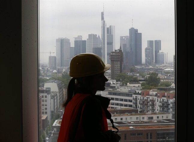 A woman looks out of a window in the eleventh floor of the construction site of the new headquarters of the European Central Bank during a media tour in Frankfurt, Germany, Tuesday, April 29, 2014. The ECB is supposed to move into the building by the end of 2014 (AP Photo/Michael Probst)